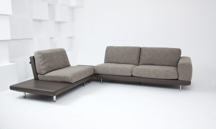Designer grey fabric corner sofa with leather details and elegant steel legs in size 285/225 cm by Urvission Interiors price £2704