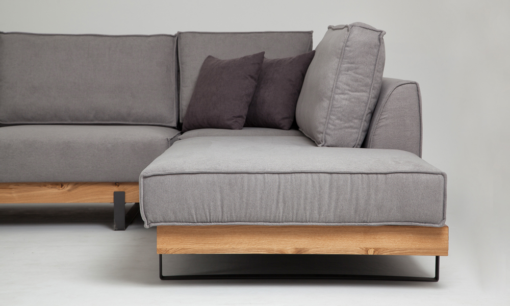 Modern grey fabric corner sofa with wood elements and elegant black steel legs in size 300/230cm by Urvission Interiors price £2833