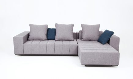 Designer grey fabric corner sofa with blue cushions and elegant steel legs in size 290/190cm by Urvission Interiors price £3116